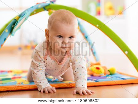 Closeup of happy seven months baby crawling on colorful playmat