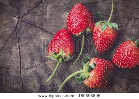 Strawberry berries fresh from the garden out of the red. Placed on a wooden floor