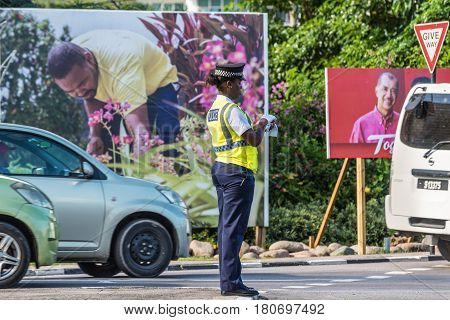 Victoria Mahe Seychelles - December 16 2015: A female creole police woman checking the traffic in the city of Victoria in Mahe island in the republic of Seychelles Indian ocean.