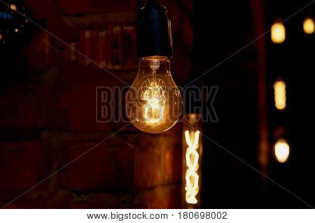 Edison light bulb hanging on a long wire. Cozy warm yellow light. Retro