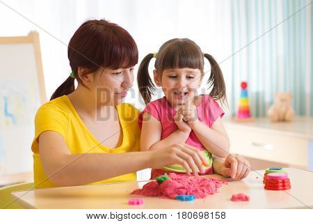 Cute child girl and mother playing with kinetic sand at home