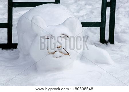 The figure of funny cat is made of white snow. Eyes whiskers mouth made of twigs. Back cat metal fence and metal.