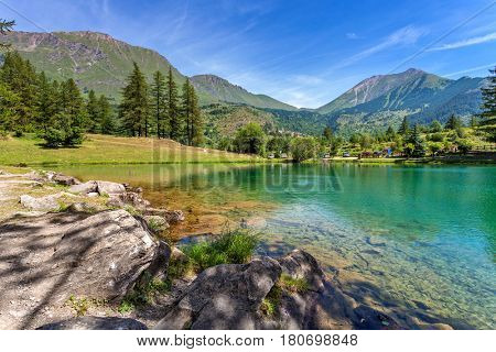 Small alpine Lake Laux among mountains in Piedmont, Northern Italy.