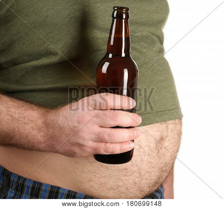 Man with big belly holding bottle of beer on white background