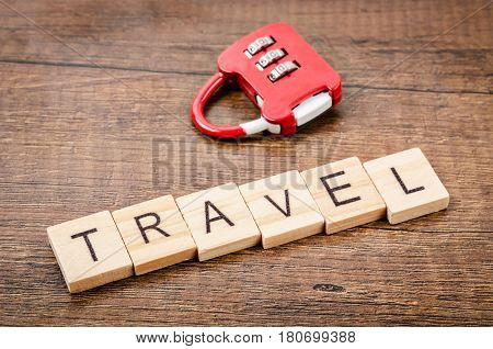 Travel word write on wooden cube with red combination lock on wooden background