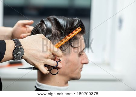 Man getting a professional haircut in salon. Professional service