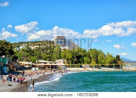 ALUSHTA, RUSSIA - MAY 15, 2016: Tourists sunbathe and swim at the beach. Alushta is a well-known resort in the Crimea.