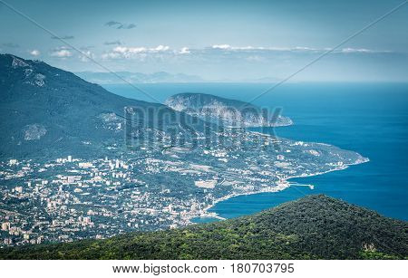 Aerial view of city of Yalta from the Mount Ai-Petri. Ayu-Dag or Bear Mountain in the background. Landscape of Crimea Russia.
