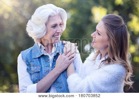 Feeling positive next to you. Delighted young smiling woman walking in the square while expressing care and hugging old mother