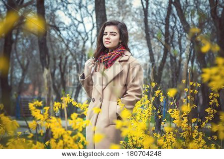 Beautiful teen girl, wearing trendy oversize beige coat and colorful scarf, walking in a spring park near blooming bushes with yellow flowers