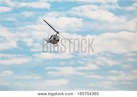White helicopter flying in the blue sky with clouds