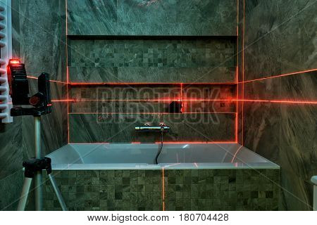 Laser measurement during bathroom renovation. Construction tools and equipment.