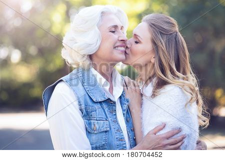Exchanging endorphins . Positive amused happy woman enjoying walk in the park while expressing love and kissing aged mother