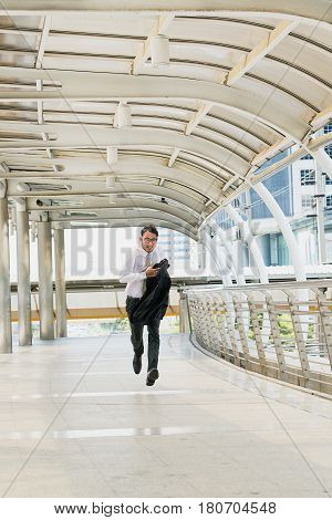 Young business man is hurrying and running on sidewalk in modern city building; Asian people lifestyle concept