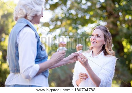 Happiness in details. Young smiling optimistic woman enjoying the weather outdoors while expressing joy and holding ice cream with old mother