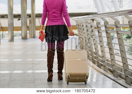 Young Asian Woman Carries Luggage Suitcase On Wheels At Sidewalk