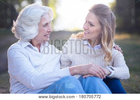 Enjoying conversation outdoors. Positive easygoing young woman enjoying picnic and expressing love while talking to aged mother
