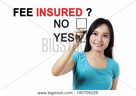 Picture of a beautiful woman using a pen while choosing a yes option to a question of fee insured on the whiteboard