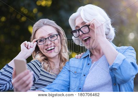 Say hey to followers. Smiling supportive aging woman walking outdoors while expressing care and hugging with young daughter