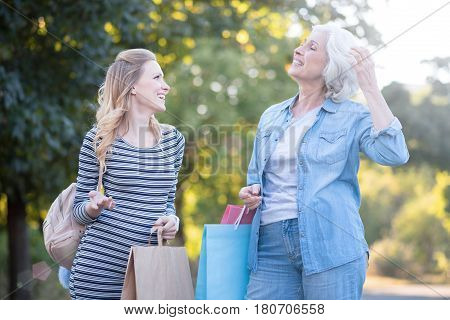 Full of irresistibility. Cheerful caring elderly woman walking in the park while expressing delight and enjoying purchases with pregnant daughter