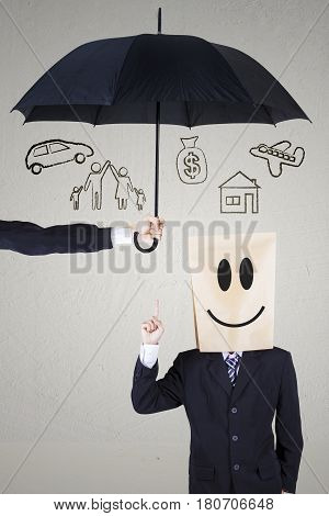 Image of businessman with cardboard head thinking of idea while pointing his dreams under umbrella. dreams insured concept