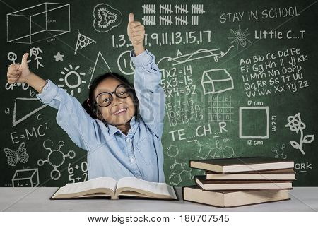 Portrait of cute schoolgirl showing ok gesture while sitting in front of book with scribble on chalkboard