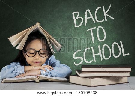 Portrait of elementary student reading a book with back to school text on chalkboard