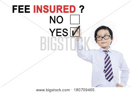 Picture of little boy using a pen while choosing a yes option to a question of fee insured on the whiteboard