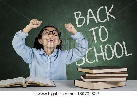 Portrait of little girl celebrating her success with back to school word on the chalkboard
