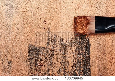 Make-Up Brush on golden painted Surface with Place for Text