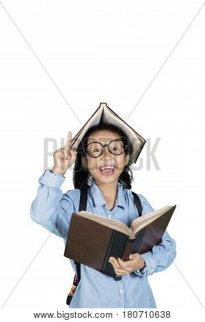 Portrait of little student gets idea while holding a book in the studio isolated on white background