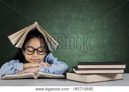 Portrait of little student reading a book while sitting in front of desk with textbook over her head