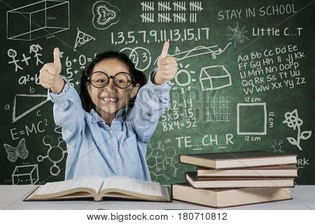 Portrait of little student showing ok sign while sitting with scribble and doodle on chalkboard