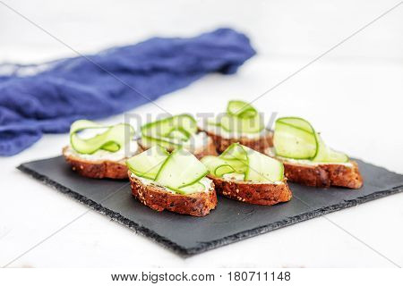 Sandwiches with cheese feta and cucumber on shale board. The concept of food and vegetarianism.