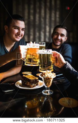 Friends Drinking Beer And Clinking Glasses At Bar Or Pub