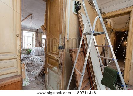 View of room of the apartment during under renovation remodeling and construction. Ladder garbage of construction materials and electric meter during on disassembling floors and walls.