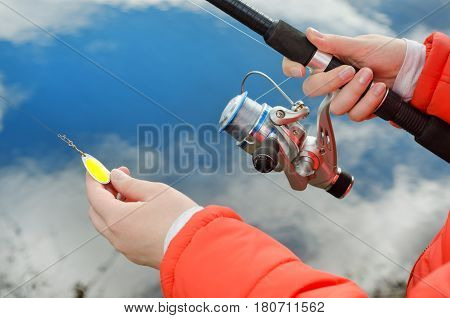 Female Hands Holding A Fishing Rod And Lure.
