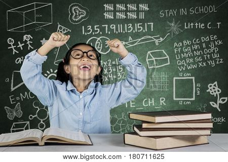 Portrait of primary student lifting hands as her success expression with book on the desk