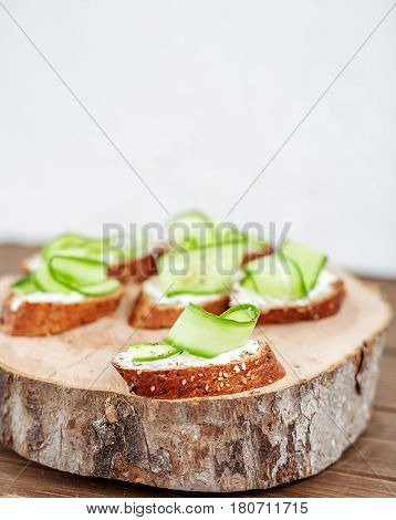 Snacks with cheese feta and cucumber on a wooden board. The concept of food and vegetarianism.