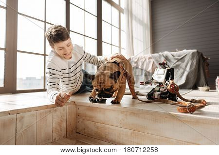 I will check. Smiling teenager patting his home pet that is standing between robot and boy, bowing head