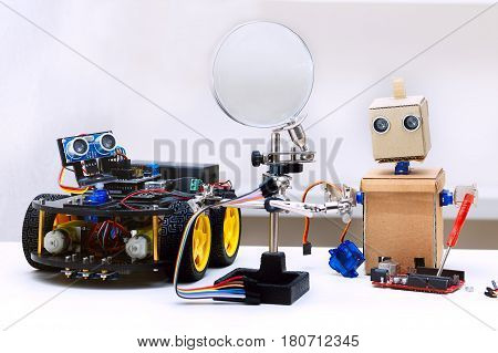Robot with arms and robot with wheels are on the table