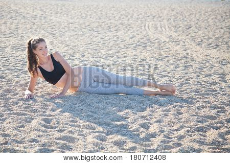 beautiful girl engaged in fitness Yoga on the beach