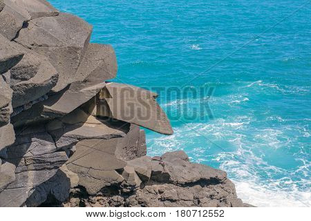 Rock Formation and the Deep Blue Sea: close up of a rock formation with a protruding stone, and crystal clear ocean