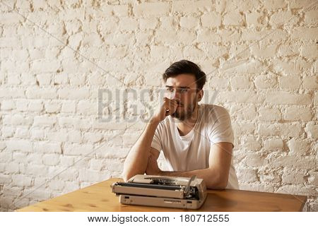 Journalist sit at the table with typewriter and think about new article. Creative crisis concept. Handsome man in white t-shirt hold chin and look away with white brick wall background. Copy space