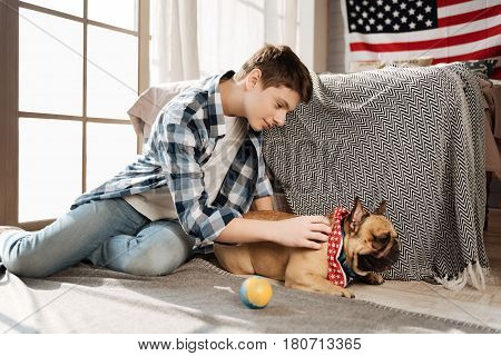 Hug me. Attractive smart boy keeping right hand on his dog leaning left hand on the floor while looking downwards