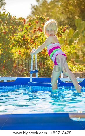 Happy Healthy Child In Swimwear Standing In Swimming Pool