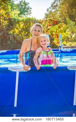 Smiling Active Mother And Daughter In Swimming Pool
