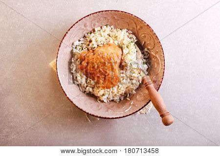 Herby rice with spicy chicken thigh in a bowl overhead shot