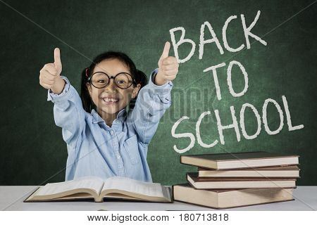 Portrait of student sitting in front of book on desk while showing ok gesture with back to school word on chalkboard