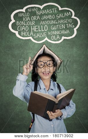 Portrait of little student pointing language lesson over her head while holding a book